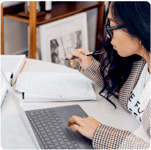 An image of a woman studying in front of her laptop and notebook